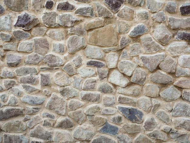 Mozaika z kamieni, cement. kamienna ściana. tekstura szarego granitu. nierówna skalna powierzchnia posadzki, ozdobna płytka elewacji budynku.