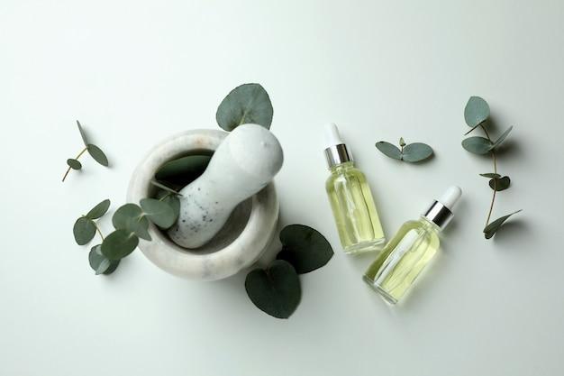 Moździerz z butelkami eukaliptusa i kroplomierzem oleju na białym tle