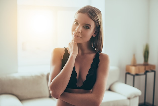 Może możesz zostać dzisiaj w domu? piękna młoda kobieta w czarnej bieliźnie patrząc na kamerę stojąc przed oknem w domu