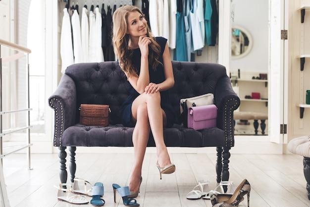 Może potrzebuję innej pary? piękna młoda kobieta wygląda na zamyśloną siedząc na kanapie w sklepie odzieżowym