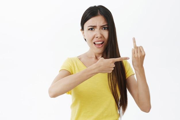 Może propozycja. wkurzona i zdezorientowana atrakcyjna europejka w żółtym t-shircie marszczy brwi i kłóci się