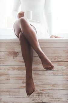 Może przerwa na kawę? przycięty obraz wspaniałej młodej afrykańskiej kobiety z pięknymi nogami siedzącej na parapecie i trzymającej filiżankę kawy