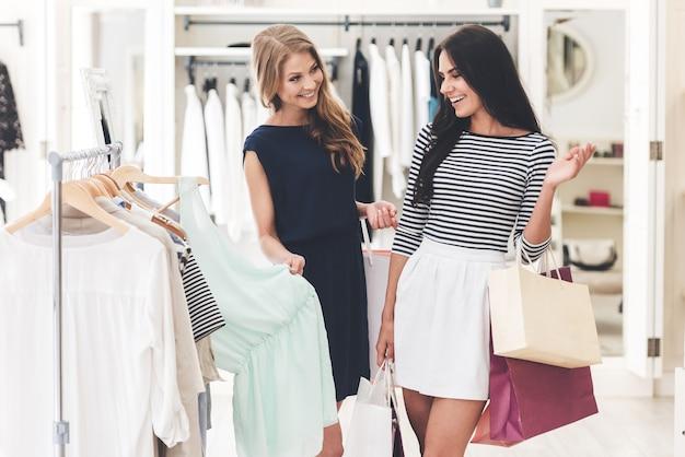 Może ta sukienka? dwie piękne kobiety z torbami na zakupy, patrzące na siebie z uśmiechem, stojące, słysząc wieszak w sklepie odzieżowym