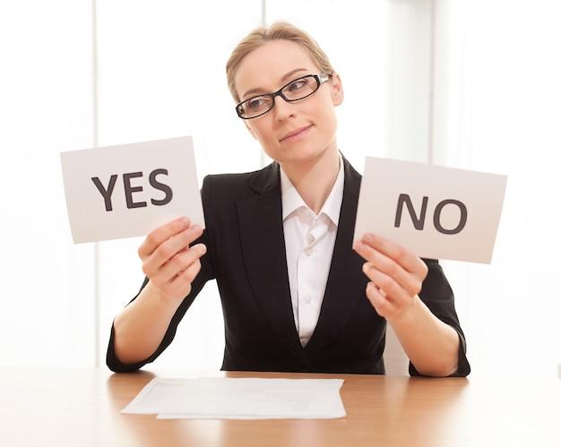 """Może tak? rozważna dojrzała kobieta w formalnym stroju siedzi przy stole i trzyma papiery z napisem """"tak"""" i """"nie"""""""