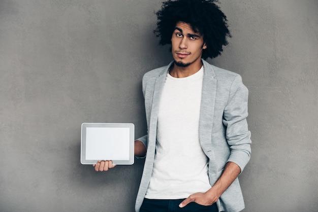 Może to ci pomoże? młody afrykanin trzymający cyfrowy tablet z kopią miejsca podczas stania