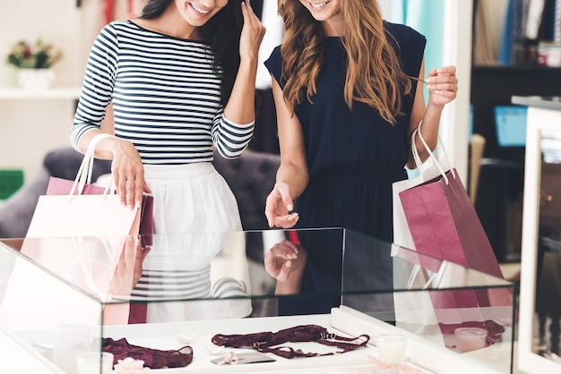 Może to jest jeden? zbliżenie dwóch pięknych kobiet z torbami na zakupy patrzących na prezentację bielizny z uśmiechem stojąc w sklepie