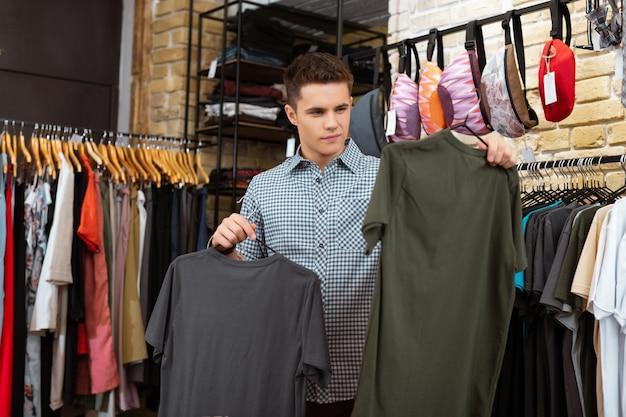 Może to. spokojny, przemyślany młody człowiek, przyglądający się z uwagą pięknym ubraniom w modnym sklepie, wybierając najlepszą koszulkę