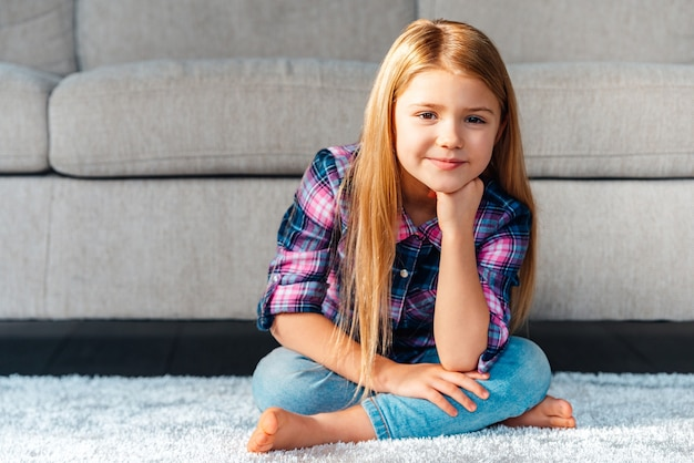 Może zagrać? wesoła dziewczynka patrząc na aparat z uśmiechem siedząc na dywanie w pozycji lotosu w domu
