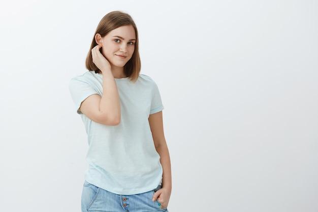 Możemy chwilę porozmawiać. nieśmiała, słodka i delikatna atrakcyjna młoda brunetka z krótkimi fryzurami, strzepująca włosy za uchem i patrząca czule z lekkim ładnym uśmiechem, pozująca na szarej ścianie