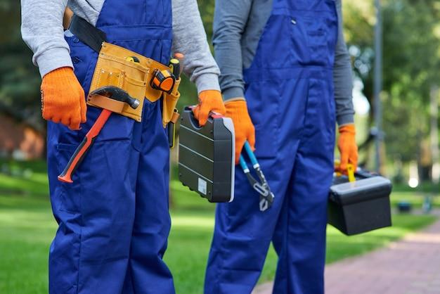 Możemy ci pomóc. mężczyzna budowniczy noszący pasek narzędziowy niosący skrzynkę narzędziową na placu budowy