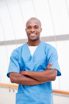 Możesz mi całkowicie zaufać. pewny siebie młody afrykański lekarz w niebieskim mundurze, patrzący w kamerę i trzymający skrzyżowane ręce