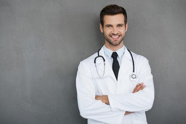 Możesz mi całkowicie zaufać. pewny siebie młody lekarz w białym mundurze, patrzący w kamerę i trzymający skrzyżowane ręce, stojąc na szarym tle