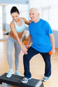 Możesz to zrobić! pełna długość pewnej siebie fizjoterapeutki pracującej ze starszym mężczyzną w klubie fitness
