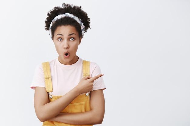 Możesz to zrobić. portret zachwyconego, podekscytowanego, przystojnego afroamerykanina w żółtych ogrodniczkach i opasce na głowę, wskazującego w prawo, zagiętych ust i wpatrującego się podekscytowany, zdumiony na szarą ścianę