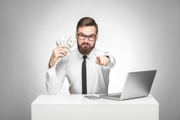 Możesz zarabiać pieniądze! portret przystojny zadowolony brodaty młody szef w białej koszuli i czarnym krawacie siedzi w biurze, wskazując palcem i trzymając wentylator pieniędzy, patrząc na kamerę, kryty na białym tle