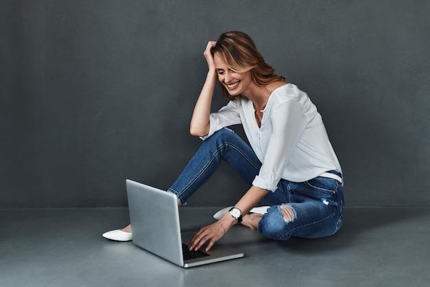 Możesz znaleźć wszystko w internecie. atrakcyjna młoda kobieta w stroju casual, korzystająca z komputera i uśmiechająca się siedząc na podłodze na szarym tle