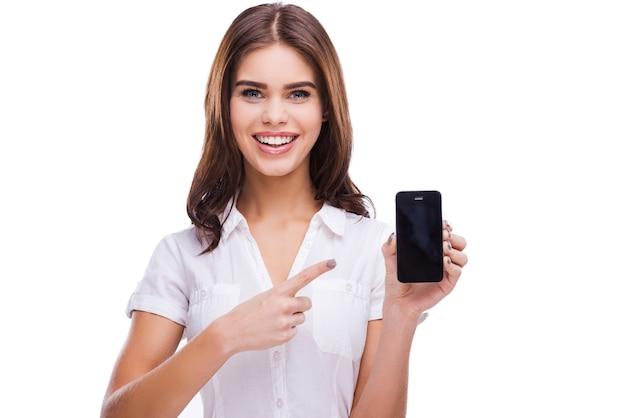 Możesz zobaczyć swoją reklamę tutaj. piękne młode kobiety trzymające telefon komórkowy i wskazujące na niego, stojąc na białym tle