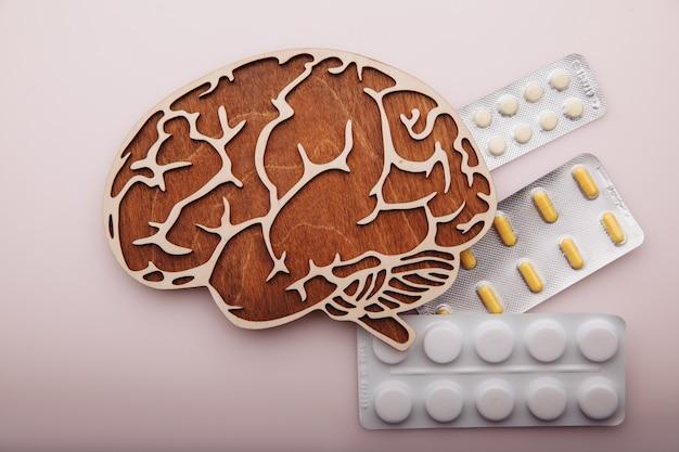 Mózg i pigułki na białym tle na różowym tle koncepcji demencji
