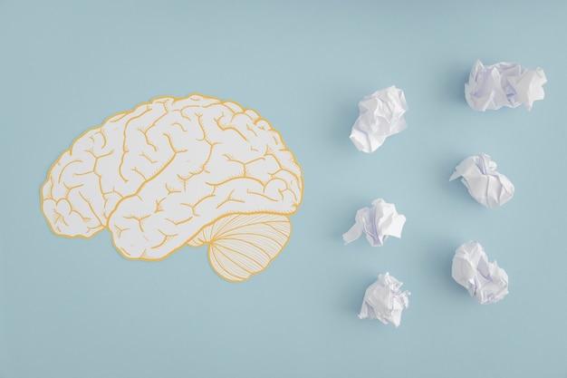 Mózg wycinanka z białymi zmiętymi papierowymi piłkami na popielatym tle