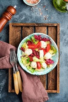 Mozzarella, pomidor i mieszanka świeżych liści sałat, ciemna powierzchnia, widok z góry.