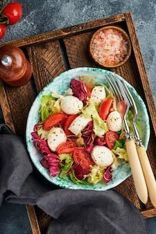 Mozzarella, pomidor i mieszanka świeżych liści sałat, ciemne tło, widok z góry. makieta.