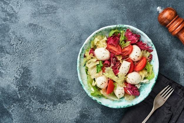 Mozzarella, pomidor i mieszanka świeżych liści sałat, ciemne tło