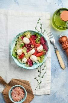 Mozzarella, pomidor i mieszanka świeżych liści sałaty, łupkowy kamienny stół tło, widok z góry. makieta.