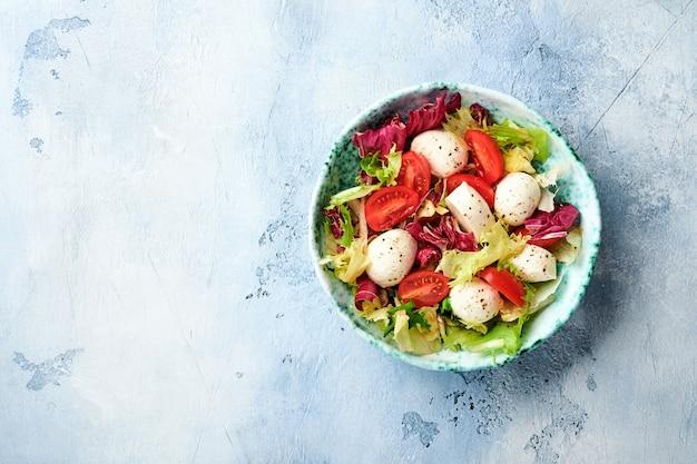 Mozzarella, pomidor i mieszanka świeżych liści sałaty, łupkowy kamienny stół tło, widok z góry.