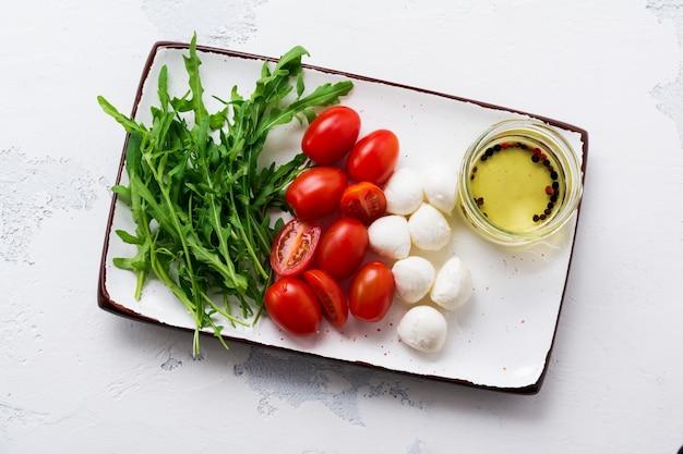 Mozzarella, pomidorki koktajlowe i rukola podawane na białych prostokątnych talerzach ceramicznych na szarej faktury. leżał na płasko