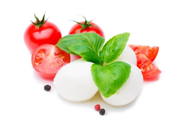Mozzarella, świeże pomidory i liście bazylii na białym tle