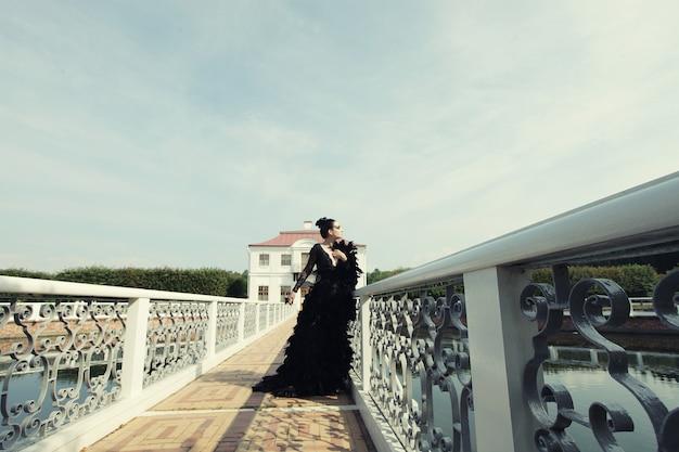 Mroczna księżniczka na moście. modelka pozowanie w parku lato.