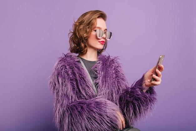 Mrożąca krew w żyłach dziewczyna o ciemnobrązowych włosach ubrana w miękkie, błyszczące futro trzyma smartfona