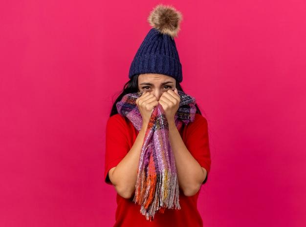 Mroźna młoda, chora kobieta ma na sobie czapkę zimową i szalik zakrywający usta szalikiem patrząc z przodu na białym tle na różowej ścianie
