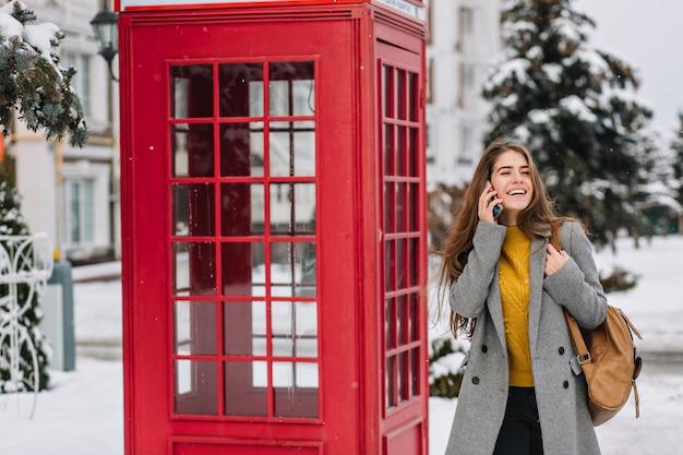 Mroźny czas zimowy radosnej młodej modnej kobiety spacerującej ulicą w pobliżu czerwonej budki telefonicznej. rozmowy przez telefon, śmiech, śnieg, oczekiwanie na boże narodzenie, wyrażanie genialnych pozytywnych emocji.