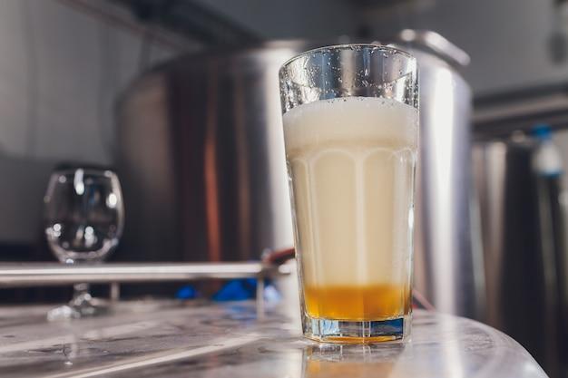 Mroźny kieliszek lekkiego piwa na blacie barowym.