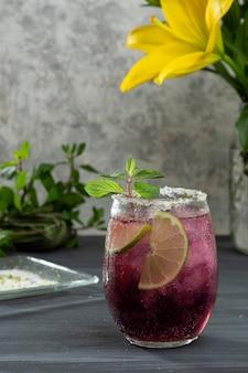 Mroźny napój z lodem i plasterkami cytryny na szarym stole i wazonie z żółtymi kwiatami