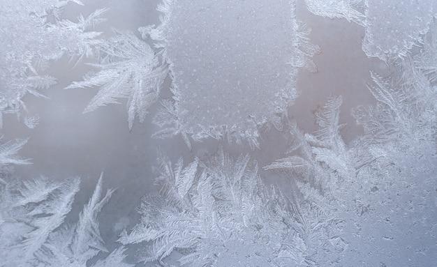 Mroźny wzór na szybie okna zimą.