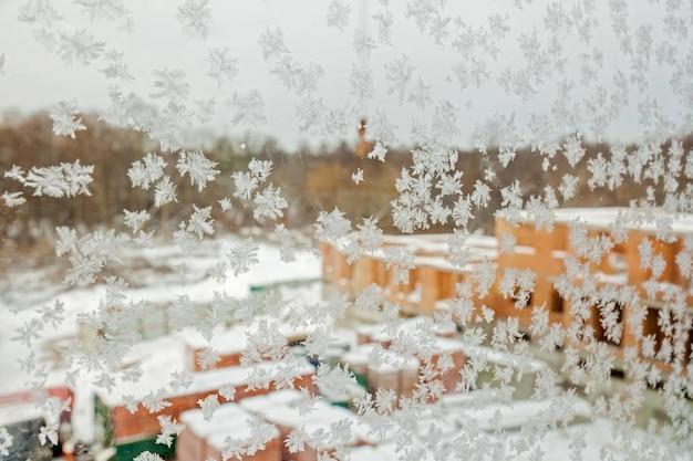 Mroźny wzór płatków śniegu na zimowym oknie na tle pozycji stojącej