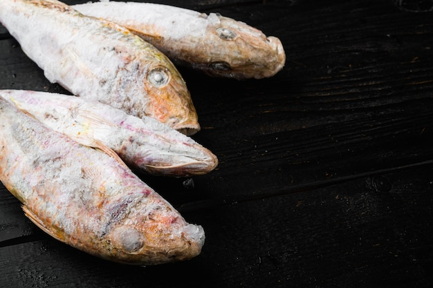 Mrożona barwena lub zestaw ryb sułtanki, na tle czarnego drewnianego stołu, z kopią miejsca na tekst