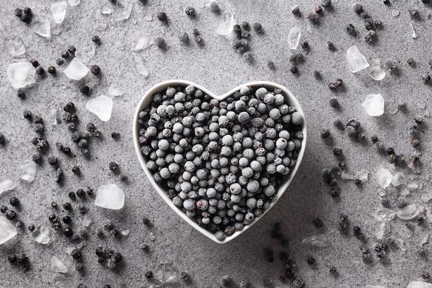 Mrożona czarna porzeczka w talerzu w kształcie serca na szarym tle widok z góry