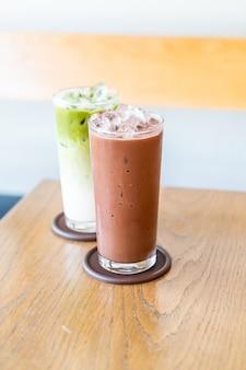 Mrożona czekolada i mrożona zielona herbata matche na stole z drewna