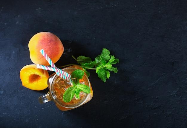 Mrożona herbata brzoskwiniowa na ciemnym tle z miętą i lodem, fajny napój na gorący sezon letni