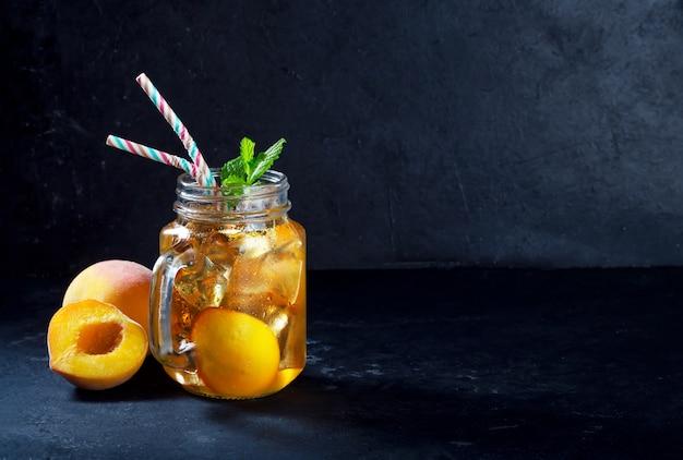 Mrożona herbata brzoskwiniowa na ciemnym tle z miętą i lodem