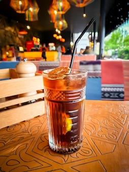 Mrożona herbata long island, mieszany napój alkoholowy w kolorze bursztynowym, highball, napój alkoholowy na stole w restauracji,