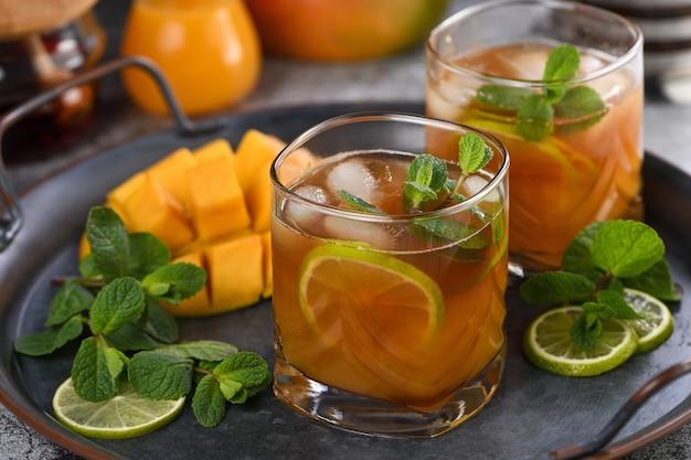 Mrożona herbata mango z limonką i miętą. orzeźwiający organiczny napój bezalkoholowy