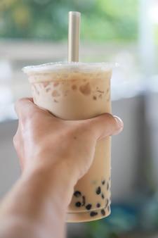 Mrożona herbata mleczna z bąbelkowym boba świeżym i słodkim napojem w stylu tajwańskim w ręku pokazuje koncepcję picia, jedzenia i picia