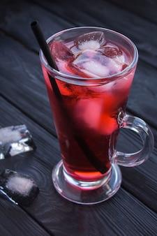 Mrożona herbata z hibiskusa lub karkade w szklance na czarnym drewnianym stole. zbliżenie.