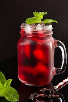 Mrożona herbata z hibiskusa lub karkade w szklance na czarnym tle. lokalizacja w pionie. zbliżenie.