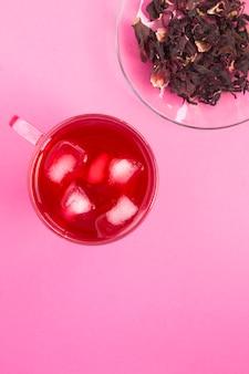 Mrożona herbata z hibiskusa lub karkade w szklance na różowym stole. widok z góry. skopiuj miejsce.
