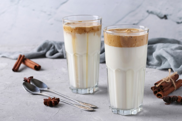 Mrożona kawa dalgona w wysokich szklankach na jasnoszarym betonie